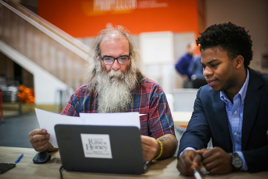 Capstone Raw Honey founder David Young, left, worked with Carlos Wilson (BSM/MACCT '16) to upgrade his accounting system as part of an innovative service learning collaboration between the Freeman School and Propeller, a nonprofit that supports social ventures. (Photo by Jennifer Zdon)