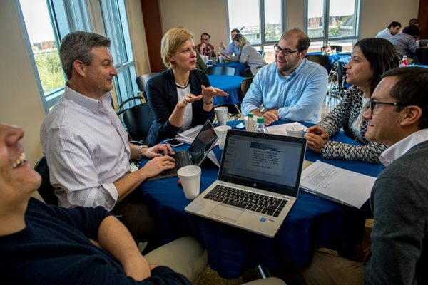 Indrė Petrukaitienė, center, an executive MBA student from the Baltic Management Institute in Vilnius, Lithuania, works on a group project with teammates during a breakout session on Wednesday, Jan. 25. (Photo by Paula Burch-Celentano)